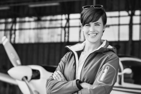 Smiling confident woman posing with her airplane in the hangar before departure, aviation and light aircrafts concept Banque d'images