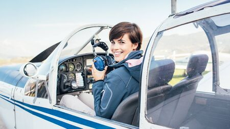 Smiling female pilot in the light aircraft cockpit, she is holding aviator headset and checking controls Banque d'images