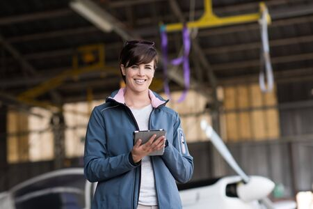 Smiling female pilot connecting with a digital tablet and using aviation apps before departure, travel and aviation safety concept