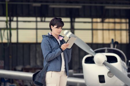 Confident female pilot in the hangar doing a pre-flight preparation, she is connecting and using aviation apps on her digital tablet, propeller plane on the background