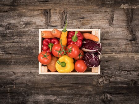 Fresh tasty red and yellow vegetables in wooden crates on a rustic wooden table