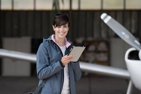 Confident woman in the hangar preparing before departure, she is using aviation apps on her tablet and smiling at camera, light aircraft on the background Banque d'images