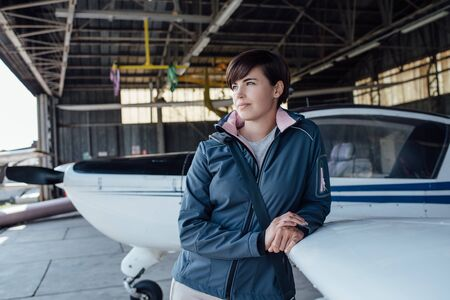 Confident young female pilot leaning on an airplane wing and looking away, she is posing in the airport hangar
