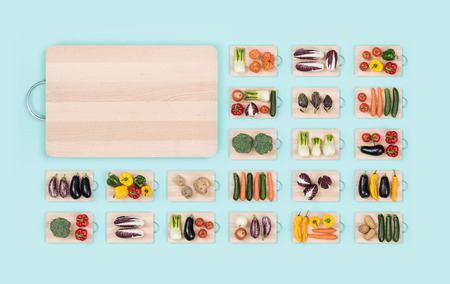 Fresh organic vegetables assortment on wooden chopping boards and copy space: healthy eating and vegan food concept