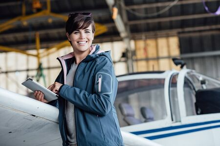 Smiling female pilot connecting with a digital tablet and using aviation apps, she is preparing before a flight, travel and aviation safety concept Banque d'images