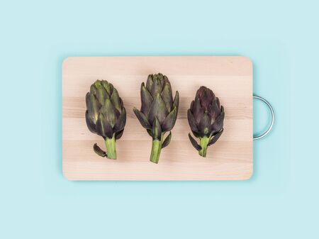 Fresh artichokes on a chopping board, food preparation and healthy eating concept