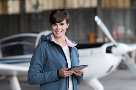 Confident female pilot in the hangar preparing before departure, she is using aviation apps on her tablet and smiling at camera, light aircraft on the background Banque d'images