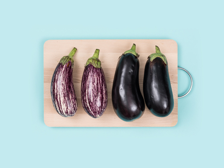 Fresh eggplants on a wooden chopping board, food preparation and healthy eating concept