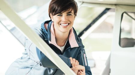 Young pilot woman leaning on an airplane and smiling at camera, travel and aviation concept
