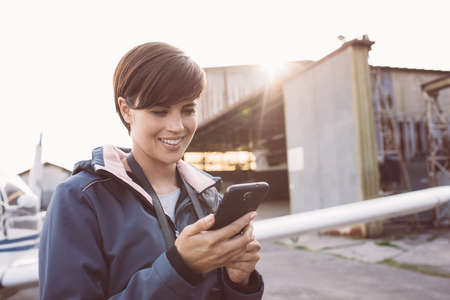 Smiling young woman at the aerodrome, she is connecting with her smartphone, hangar and airplane on the background