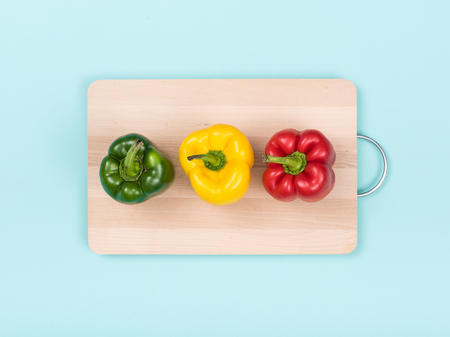 Fresh bell peppers on a wooden chopping board: healthy eating and food preparation