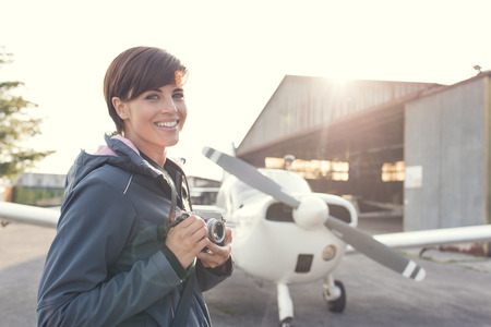 Smiling young female photographer and tourist at the airport, she is holding a digital camera, propeller plane and hangar on the background