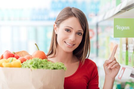 Smiling woman shopping at the supermarket and holding a grocery bag with fresh vegetables, she is buying healthy vegan food