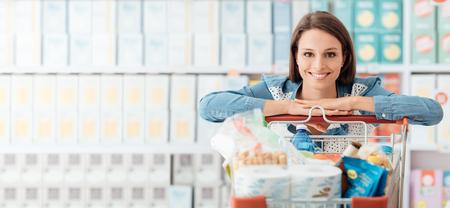 Smiling szczęśliwa kobieta korzystających zakupy w supermarkecie, ona jest oparty na pełnym wózkiem, stylu życia i koncepcji sprzedaży detalicznej