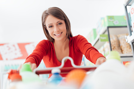 Young woman enjoying shopping at the supermarket, she is pushing a full shopping cart and smiling