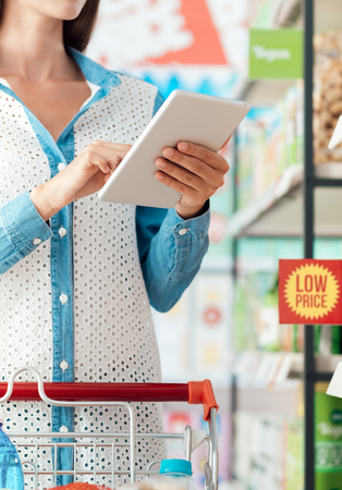 Woman doing grocery shopping at the store, she is connecting with a digital tablet, searching offers and products online