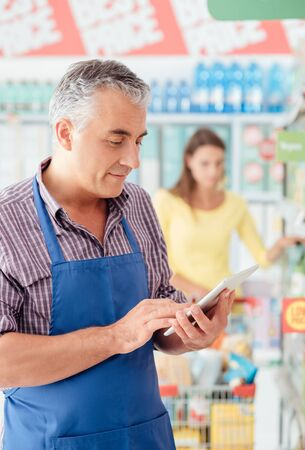 Confident supermarket clerk working with a digital tablet, technology and work concept