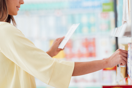 Woman doing grocery shopping at the supermarket, she is reading a list and taking products from the store shelf Banque d'images