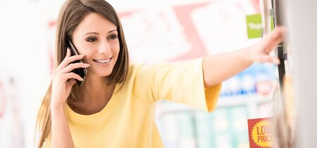 Smiling attractive young woman having a phone call at the supermarket, she is taking products from the shelf