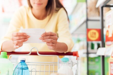 Woman doing grocery shopping at the supermarket, she is leaning on a full shopping cart and reading a list, retail and lifestyle concept Banque d'images