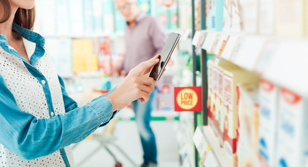 Woman shopping at the supermarket, she is searching products and offers using her phone, augmented reality and retail concept