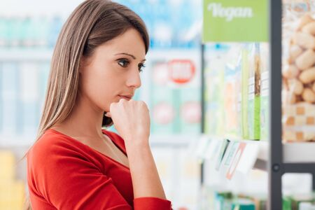 Young woman choosing products on the supermarket shelves and reading labels, she is thinking with hand on chin Banque d'images