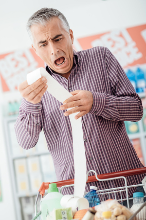 Man doing grocery shopping at the supermarket and checking a long expensive receipt, he is shocked and gasping Banque d'images