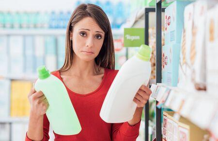 スーパーで買い物をする女性と洗剤製品を比較すると、どれが一番良いかを決めることができません