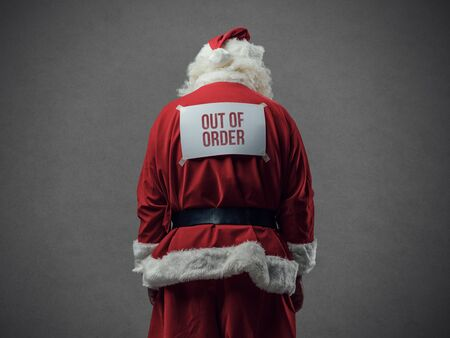Santa Claus with out of order sign on his back, he is looking down, back view