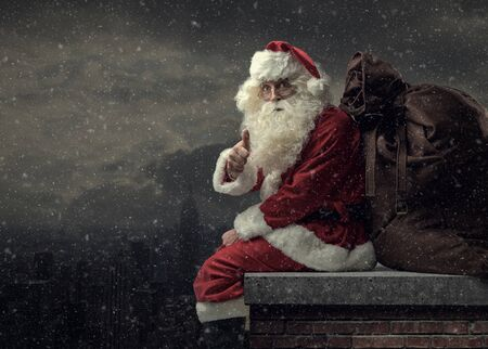 Happy Santa Claus bringing gifts on Christmas Eve: he is sitting on a roof, carrying a big sack and giving a thumbs up
