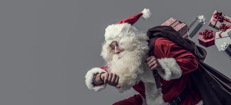 Grappige kerstman die kerstcadeautjes rent en bezorgt, hij controleert de tijd en verliest cadeaus uit zijn zak Stockfoto