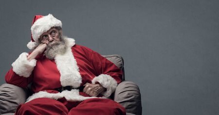 Lazy tired Santa Claus waiting for Christmas, he is sitting on the armchair at home and resting head on hand