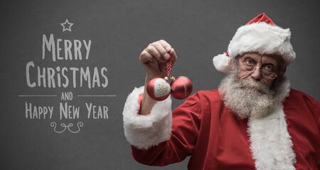 Lazy Santa Claus with sarcastic expression, he is holding two Christmas balls, Christmas card with wishes Imagens