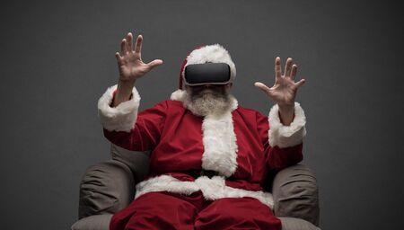 가상 현실을 경험하는 산타 클로스, 그는 VR 안경을 쓰고 가상 환경과 상호 작용합니다.