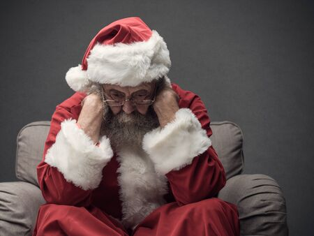 Nervous Santa Claus on Christmas Eve, he is sitting on the armchair and resting head on his hands