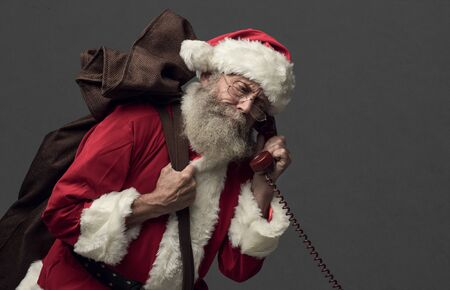 Happy Santa Claus carrying an heavy sack with Christmas gifts and answering phone calls Stock Photo