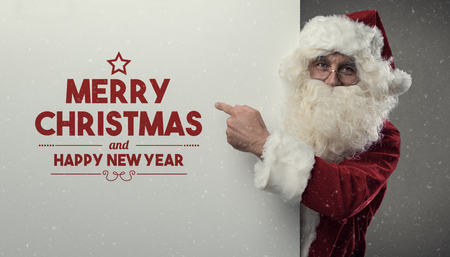 Happy Santa Claus wishing you a Merry Christmas and a Happy New Year, he is pointing and looking at camera
