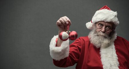 Lazy Santa Claus with sarcastic expression, he is holding two Christmas balls Imagens
