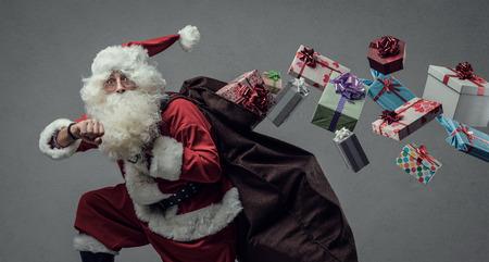 Divertido Santa Claus corriendo y entregando regalos de Navidad, él está controlando el tiempo y está perdiendo los regalos de su saco