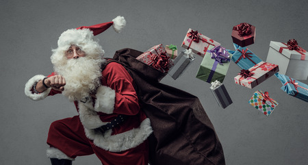 Funny Santa Claus running and delivering Christmas presents, he is checking time and losing gifts from his sack