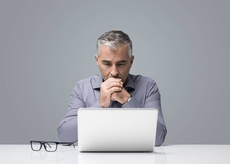 Mature businessman sitting at desk and working with a laptop, he is reading and thinking, business strategies and problem solving concept Foto de archivo