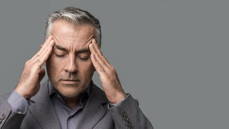 Exhausted overworked corporate businessman with head in hands, he is having a bad headache and feeling stressed Stok Fotoğraf