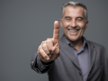Smiling businessman using a virtual interface, he is pointing with a finger Stock Photo