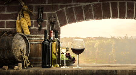 Wine bottles, wineglasses, barrels next to the cellar window and beautiful panoramic view of countryside vineyards: winemaking and wine culture concept