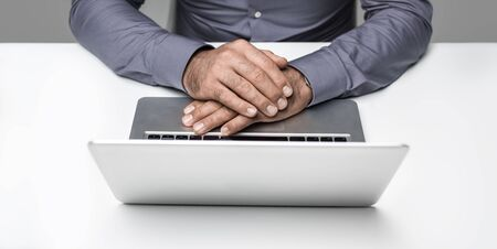 Businessman sitting at office desk and working with a laptop, he is waiting during a business meeting, hands close up Stock Photo