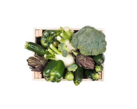 Fresh tasty green vegetables in wooden crates on white background