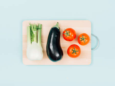 Fresh organic vegetables on a wooden chopping board, food preparation and healthy eating concept