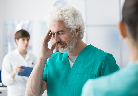 Professional doctor and surgeon working at the hospital and having an headache, he is touching his head