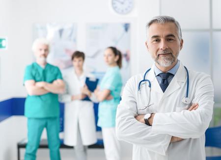 자신감이 웃는 의사 포즈와 팔을 병원 건너와 배경에 작업 의료 팀