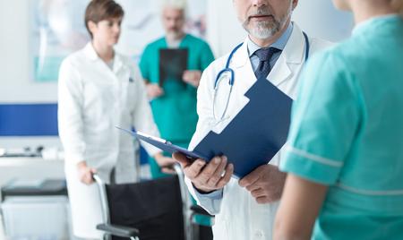 Berufsdoktor und medizinisches Personal, die am Krankenhaus arbeiten, überprüft er die Krankenblätter des Patienten